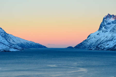 artic circle: Colourful dawn sky over arctic fjord surrounded by snowy majestic mountains northern Norway