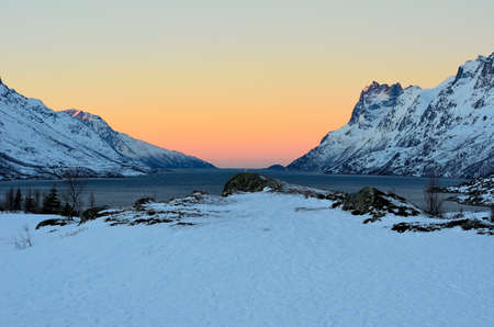 vibrant colours: Majestic snowy mountains surround arctic fjord with vibrant colours on the dawn sky in northern Norway