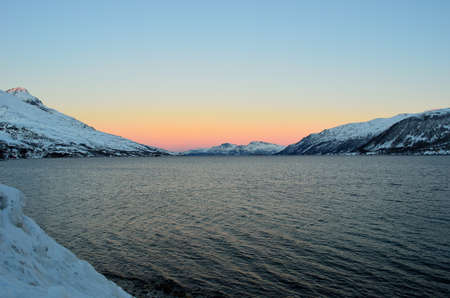 artic circle: Vibrant colours on dawn sky over cold arctic fjord water and majestic snowy mountain range in winter