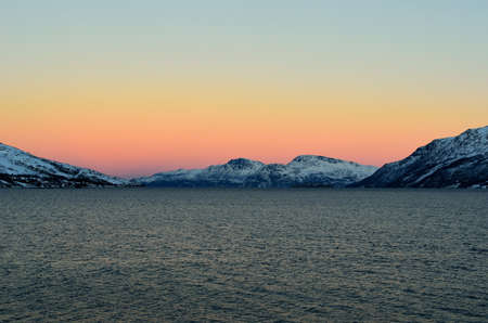 Vibrant colours on dawn sky over cold arctic fjord water and majestic snowy mountain range in winter photo