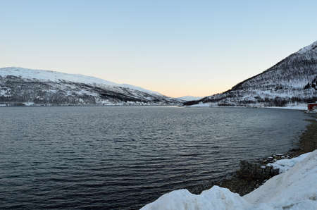 Cold fjord water surrounded by snowy mountains and vibrant dawn sky in northern Norway photo
