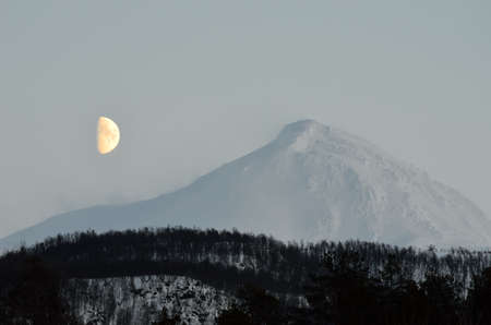 deep freeze: moon beside a majestic snowy mountain in winter