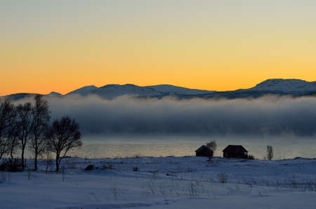 artic circle: thick ice fog over lake with orange dawn sky in winter