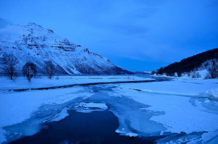sub zero: thick ice on creek and snowy mountain landscape in winter