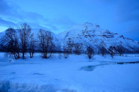 artic circle: Fresh water river leading out into the fjord covered in snow and ice in Norway