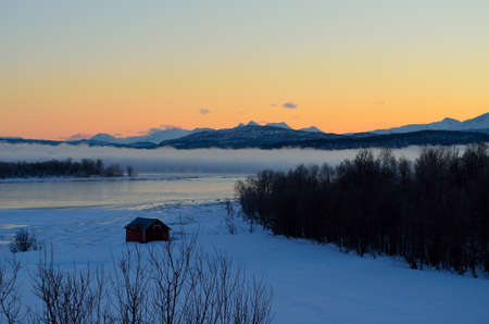 orange dawn sky behind lake covered in thick ice fog in winter photo