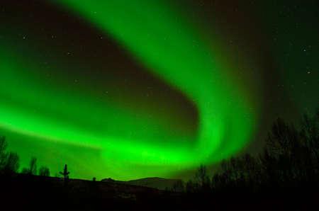 Strong green aurora borealis over a snow covered mountain in the arctic circle