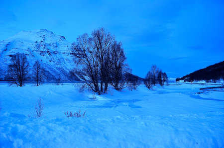 artic circle: blue winter landscaoe with creek, ice and mountain Stock Photo