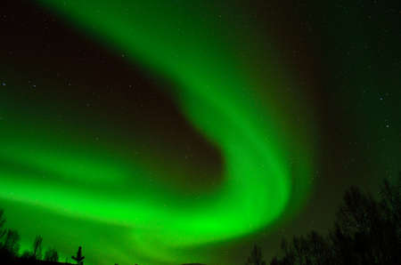 Strong green aurora borealis on the winter night sky in the arctic circle Stock Photo