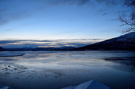 artic circle: snow and ice over winter fjord with a beautiful blue dawn sky background