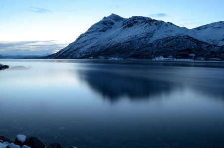 Majestic mountain reflection on fjord surface at winter in Norway photo