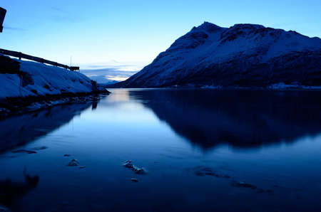 artic circle: Majestic mountain reflection on fjord surface at winter in Norway