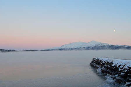 thick ice fog over fjord surface with snowy mountain, colourful dawn sky and moon in the background in winter photo