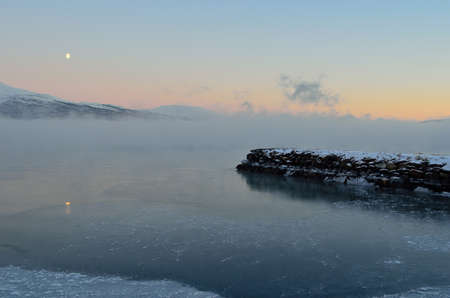 beautiful icy fjord covered in thick ice fog with moon and orange vibrant dawn sky and snowy mountain in the distance photo