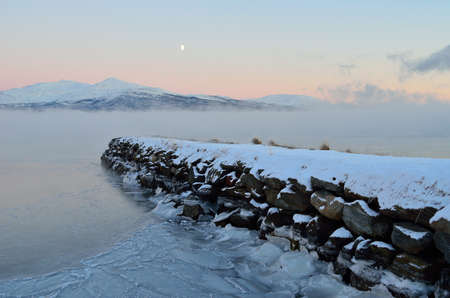 artic circle: beautiful stone pier going out in a icy fjord covered in thick ice fog with moon and orange vibrant dawn sky and snowy mountain in the distance