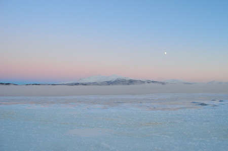 snow covered mountain: Frozen blue sea ice with thick ocean ice fog and snow covered mountain and colourful sky in the background