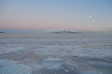 snow covered mountain: Frozen blue sea ice with thick ocean ice fog, moon and snow covered mountain and colourful sky in the background Stock Photo