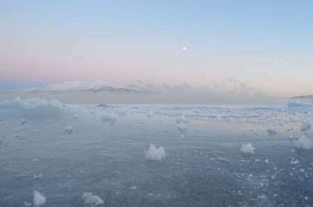 artic circle: Frozen blue sea ice with thick ocean ice fog and snow covered mountain and colourful sky in the background