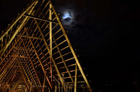 long, deep and beautiful wooden stockfish strucutre for drying fish at night time with full moon on the night sky photo