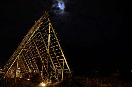stockfish: long, deep and beautiful wooden stockfish strucutre for drying fish at night time with full moon on the night sky Stock Photo