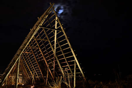 moon fish: long, deep and beautiful wooden stockfish strucutre for drying fish at night time with full moon on the night sky Stock Photo