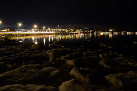 icy sea shore and beautiful fjord with city lights reflecting on the sea surface at night photo