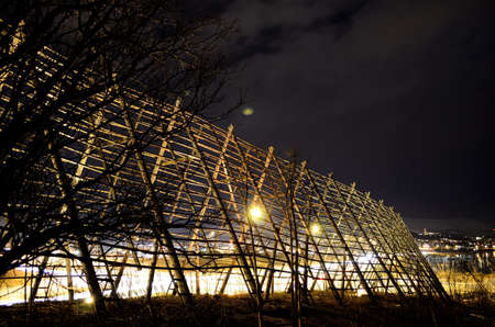 beautiful wooden stockfish drying strucutre at night time with car traffic in the background photo