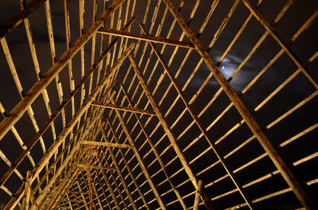 artic circle: beautiful wooden stockfish drying strucutre at night time with moonlight in the arctic circle