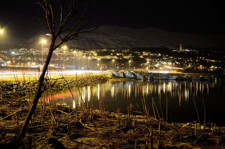 beautiful tromsoe city island at night with car traffic and light reflection on fjord surface photo