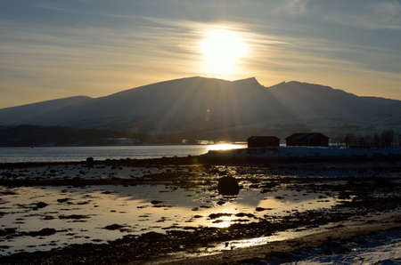 artic circle: sunshine over snowy mountain and fjord seashore