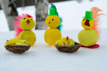 self made: Yellow homemade easter chickens with top hats and newborn in basket on snow