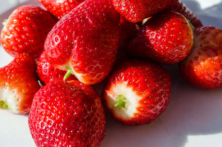 berryes: sweet red strawberries on white plate in easter sun Stock Photo