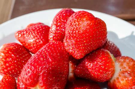 red vibrant strawberries on white platter outside in easter sun Stock Photo