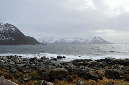 stormy windy day by the sea shore with majestic mountain in the distance on the island of Senja photo