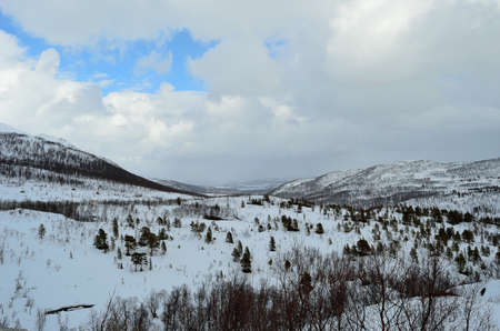 snowy mountain landscape with clouds and patch with blue sky photo
