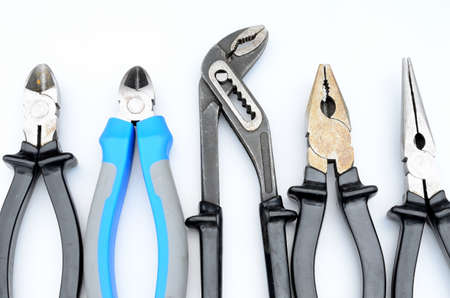 different pliers on white background photo