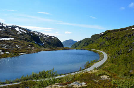 mountain lake in summer with road on side photo