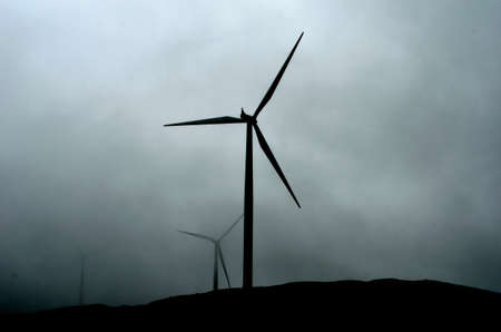 windmill on mountain top on dark and rain heavy summer day photo
