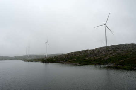 windmill on mountain in thick summer fog photo