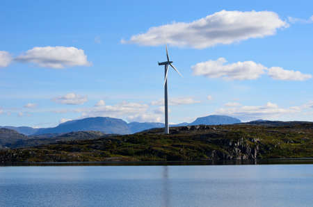 windmill on mountain top reflecting in the lake water on a sunny blue autumn day photo