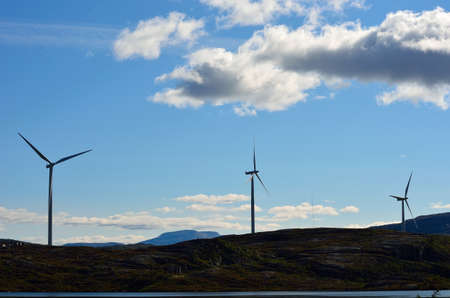 windmill farm on mountain top in autumn sun photo