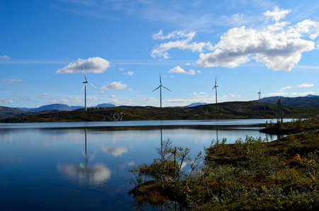 windmill farm on mountain top reflecting in the lake water on sunny blue autumn day photo