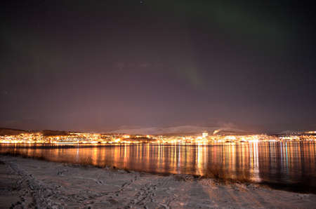 faint: faint green aurora borealis over tromsoe city fjord and city with snowy mountains in the background in winter Stock Photo