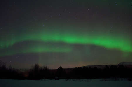 artic circle: magnificent aurora borealis over frozen river bed and snowy mountain in the cold arctic circle night