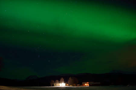 artic circle: green strong aurora borealis over field and homes in the arctic circle winter landscape