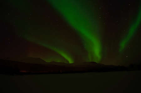 auroral: Fantastic vibrant and strong aurora borealis, northern light over snow covered mountain and frozen river bed in the arctic circle at night
