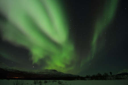 Fantastic vibrant and strong aurora borealis, northern light over snow covered mountain and frozen river bed in the arctic circle at night photo