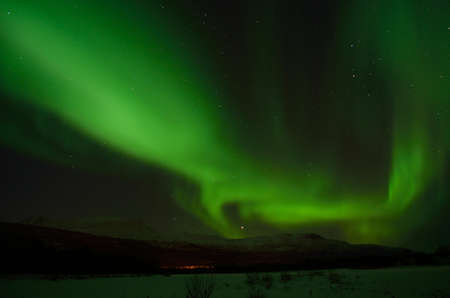 artic circle: incredible strong aurora borealis over snowy mountain and frozen river bed in winter landscape Stock Photo