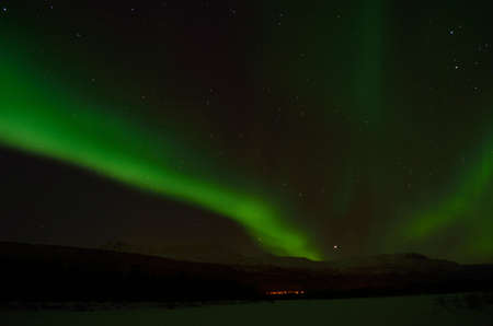 artic circle: Fantastic vibrant and strong aurora borealis, northern light over snow covered mountain and frozen river bed in the arctic circle at night