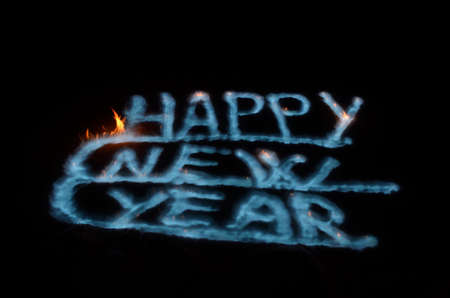 happy new year burning with blue vibrant flames on snow surface in winter photo